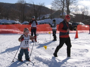 Lollipop racer from Frost Mountain Club making the turn on her second lap as her dad cheers.